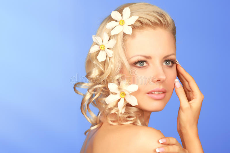 Woman with flowers in hair. Portrait of attractive young blond woman with flowers in hair, isolated on blue background stock photo