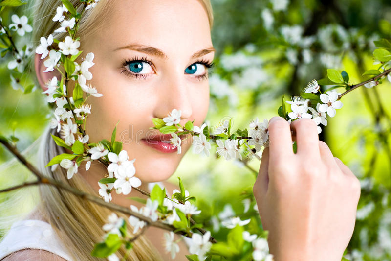 Woman by flowers on tree royalty free stock image