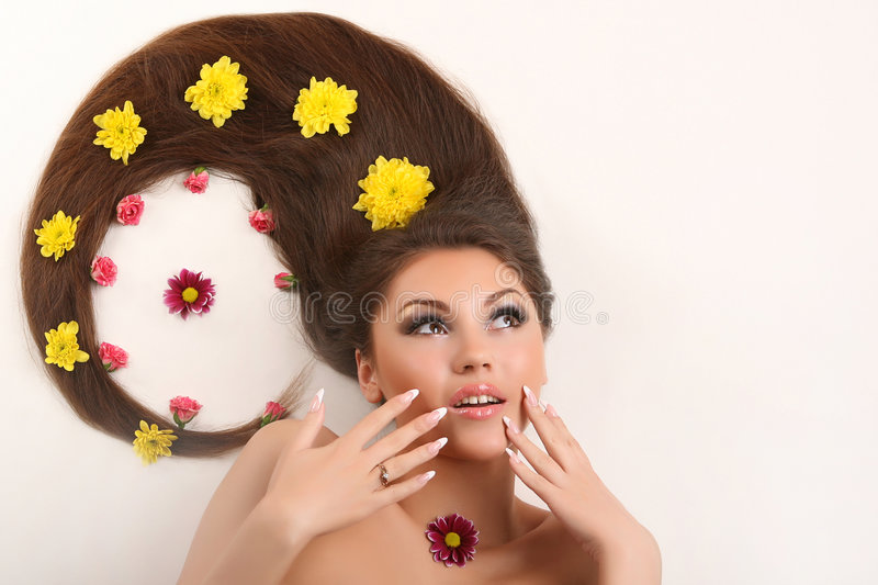 Woman with flowing hair. Attractive young woman with flowing hair and flowers on white background royalty free stock image