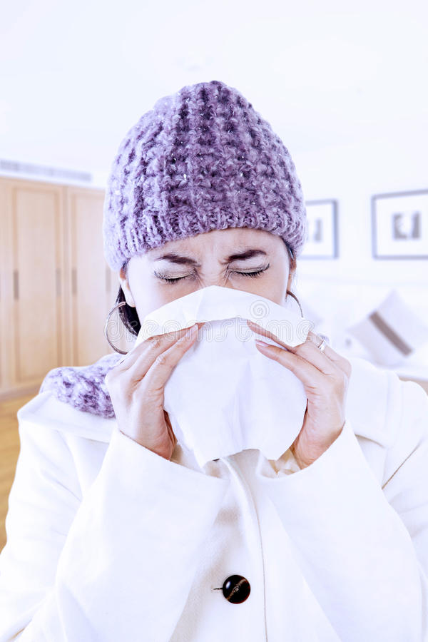 Woman with flu blowing nose at home. Asian woman with beany is blowing her nose at home stock photo