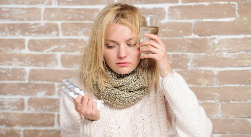Woman with flu. Unhealthy woman holding pills and water glass. Ill woman treating symptoms caused by cold or flu. Cute. Sick girl taking anti cold pills royalty free stock images