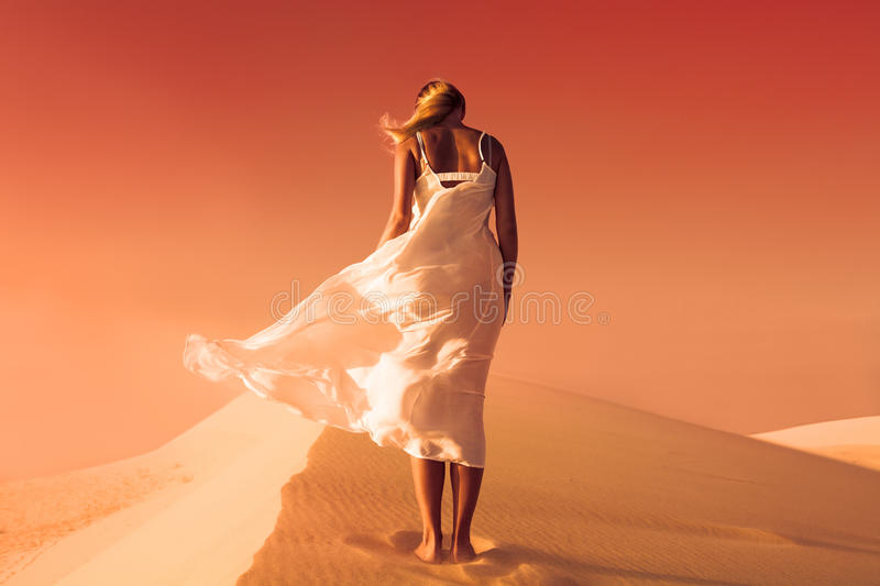 Woman in fluttering dress. Desert and sand dunes. Red sky. royalty free stock photos