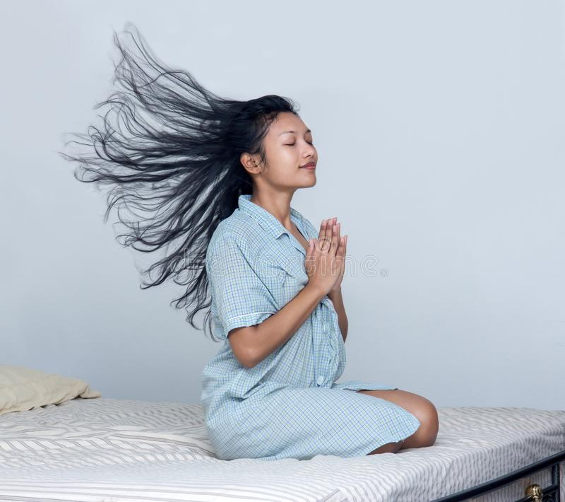Woman with flying hairs praying in bed. Woman with flying hairs praying sits on the bed stock images