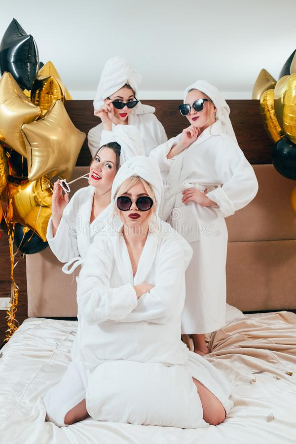 Woman folded arms doubt friends bathrobe party. Not sure. Young women with folded arms. Incredulity and doubt. Friends behind. Girls bathrobe party. Balloons royalty free stock image
