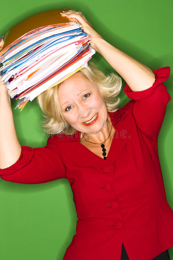 Woman with folders over head. A studio view of a middle aged businesswoman or office worker wearing a bright red blouse on a green background, holding a stack of royalty free stock images