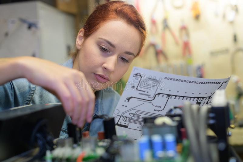 Woman following wiring instructions stock images