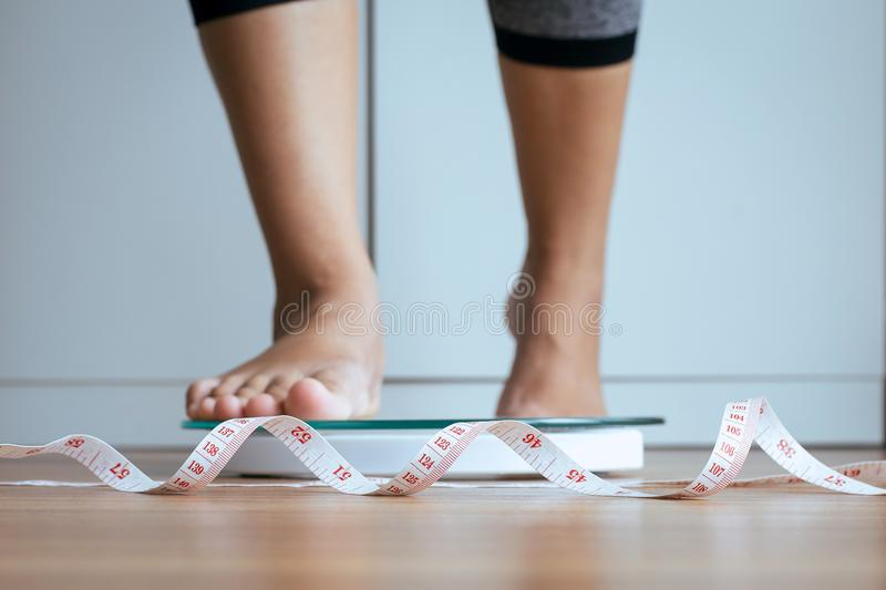 Woman foot stepping on weigh scales with tape measure in foreground,Weight loss,Body and good health concept. Woman foots stepping on weigh scales with tape stock images