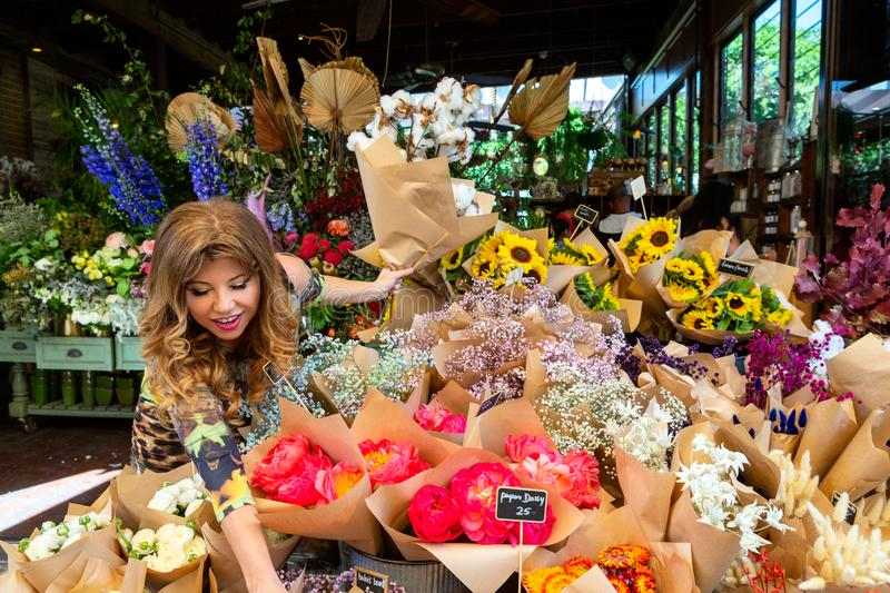 Woman on footpath choosing bunches of flowers from florist stock photos