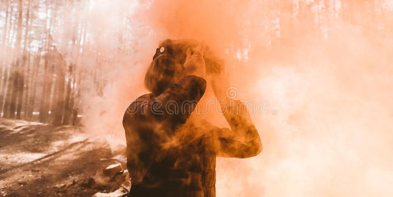 Woman in forest with virtual reality headset looking straight with orange smoke from smoke bombs. Beautiful young blond woman in forest with virtual reality royalty free stock images