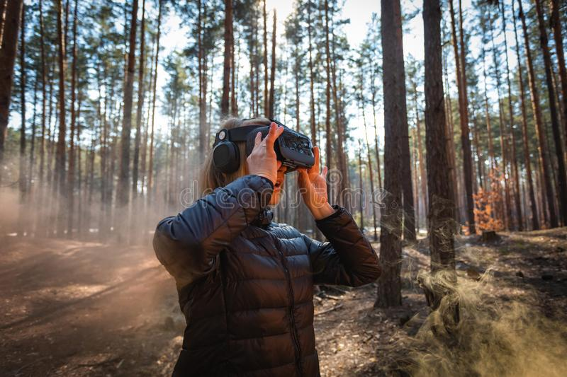 Woman in forest with virtual reality headset looking straight with orange smoke from smoke bombs. Beautiful young blond woman in forest with virtual reality royalty free stock image
