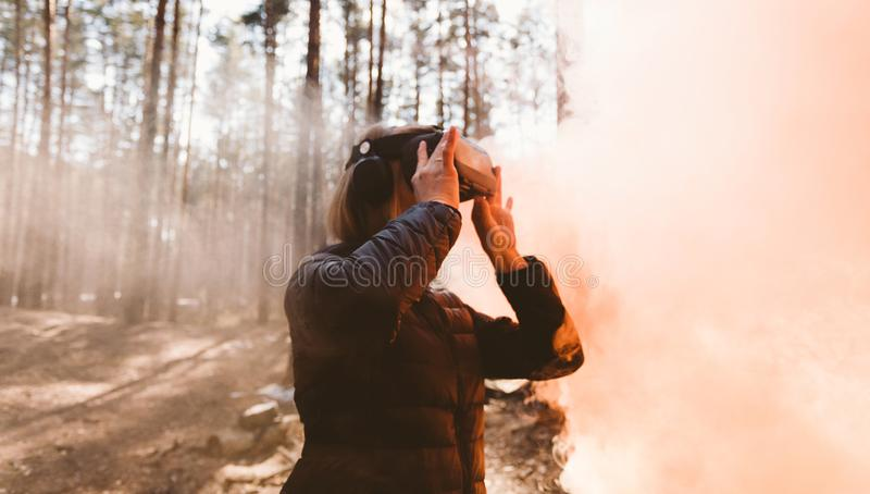 Woman in forest with virtual reality headset looking straight with orange smoke from smoke bombs. Beautiful young blond woman in forest with virtual reality stock photos