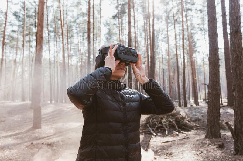Woman in forest with virtual reality headset looking straight with orange smoke from smoke bombs. Beautiful young blond woman in forest with virtual reality stock photo