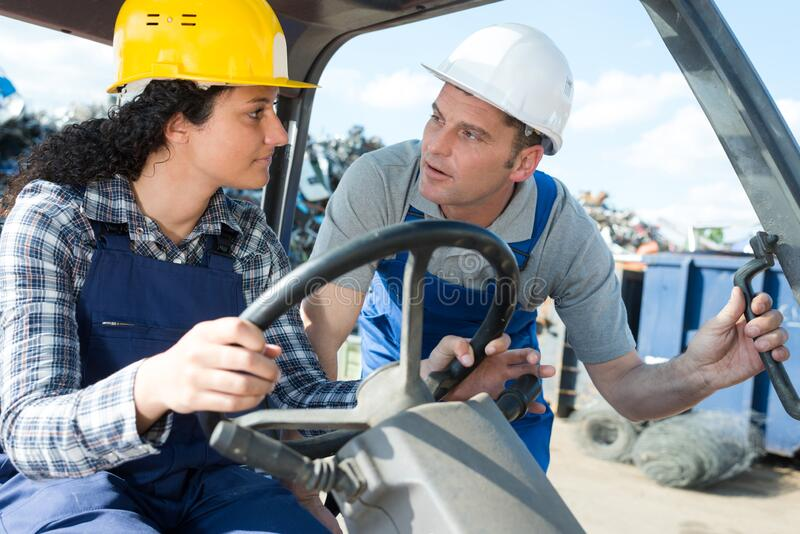 Woman forklift truck driver talking to colleague royalty free stock photography