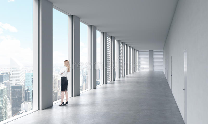 A woman in formal clothes is looking out the window. Empty modern bright clean interior of an open space office. Huge panoramic wi stock photos