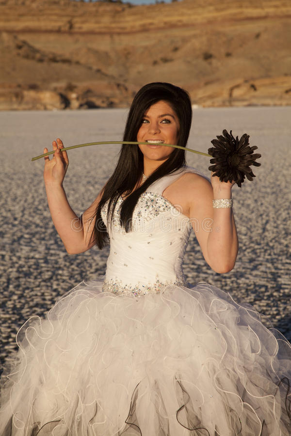 Woman formal dress ice bite flower. A woman in her formal dress with a black flower in her mouth, standing on a frozen lake royalty free stock photo