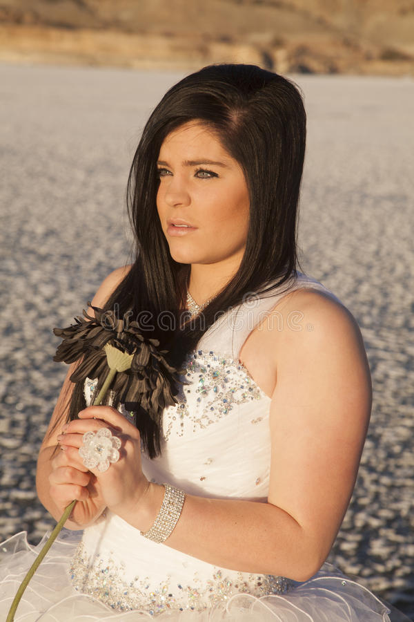 Woman formal dress ice flower look side. A woman in the outdoors looking away while holding on to her flower while standing on a frozen lake stock photography