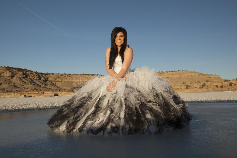 Woman formal dress ice sit smile blue sky. A woman in her formal dress with a smile on her face standing on a frozen lake in the outdoors stock images