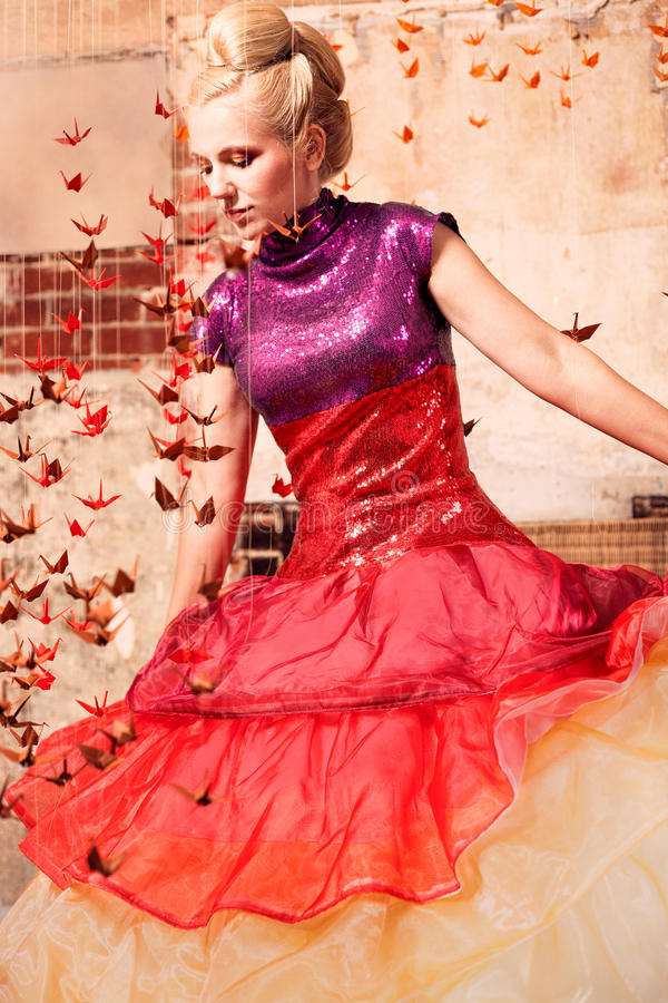 Woman in a formal dress with origami birds stock image