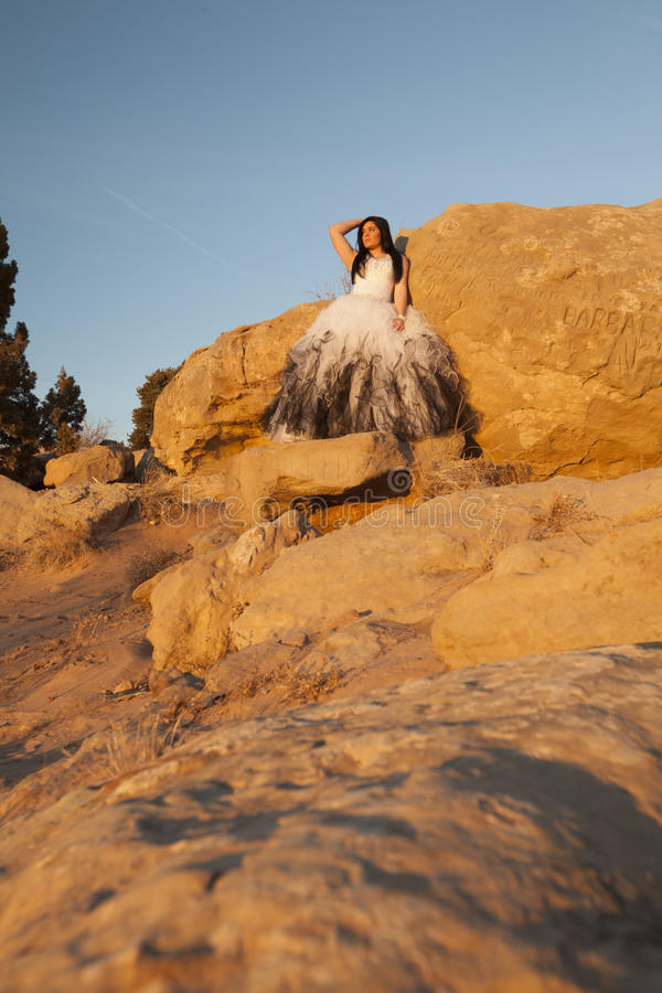 Woman formal rocks in foreground. A woman leaning up against a rock with a beautiful blue sky royalty free stock image