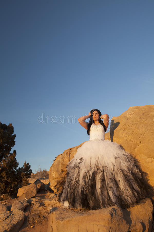 Woman formal rocks hands up blue sky. A woman in her formal dress standing on a rock looking away royalty free stock photo
