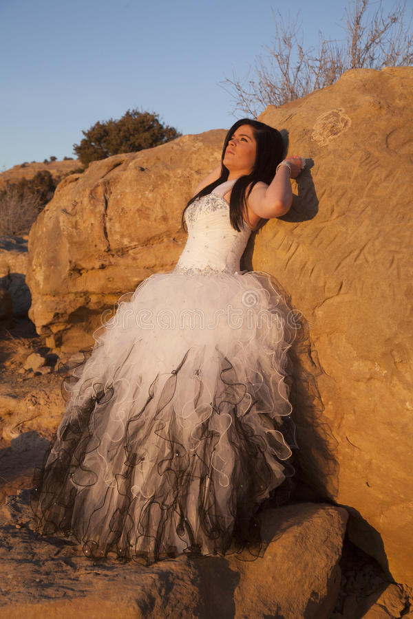 Woman formal rocks lean back hands up. A woman leaning back against a rock looking up to the sky royalty free stock image