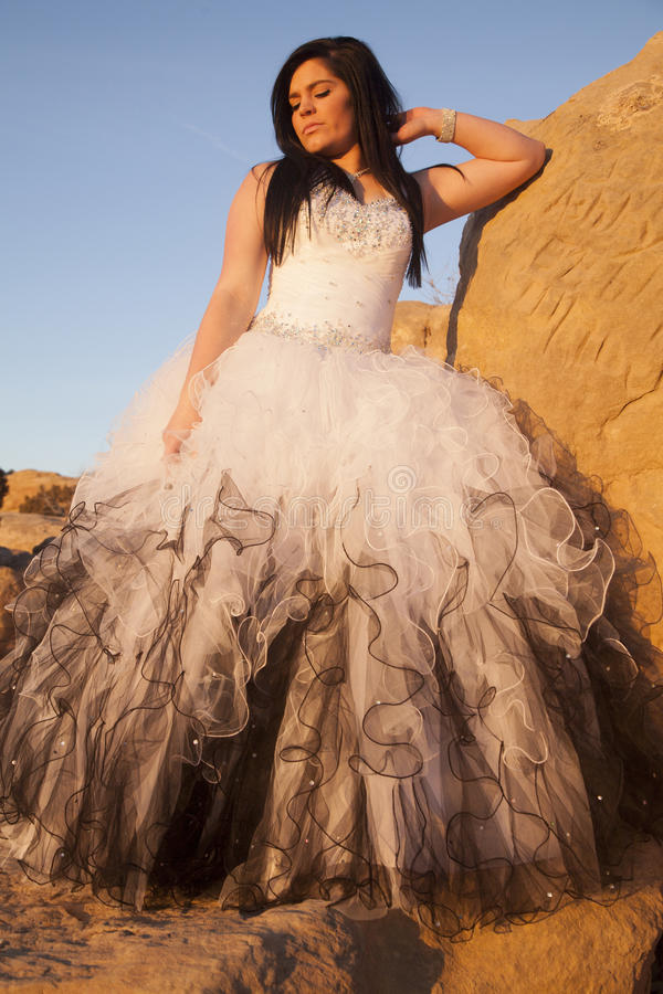 Woman formal rocks look down. A woman in her formal dress looking down, while standing on rocks royalty free stock images