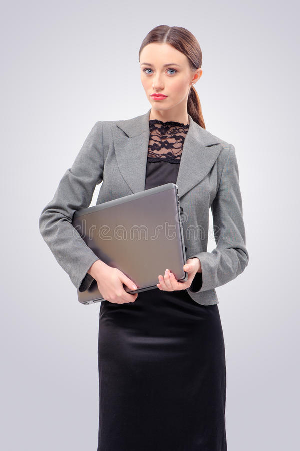 Woman in formalwear holding laptop. Beautiful young business woman in formal wear holding laptop isolated on grey background stock photography