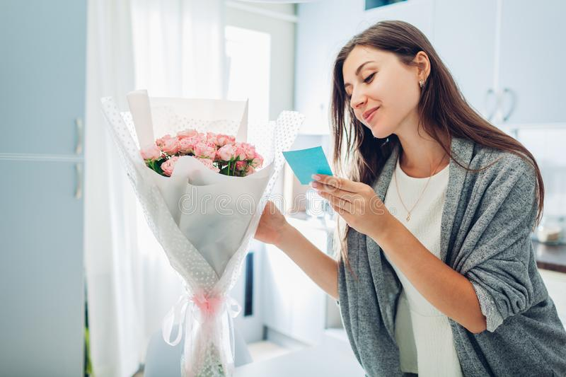 Woman found bouquet of flowers on kitchen and reading card on kitchen. Surprise. Present for holiday stock photo