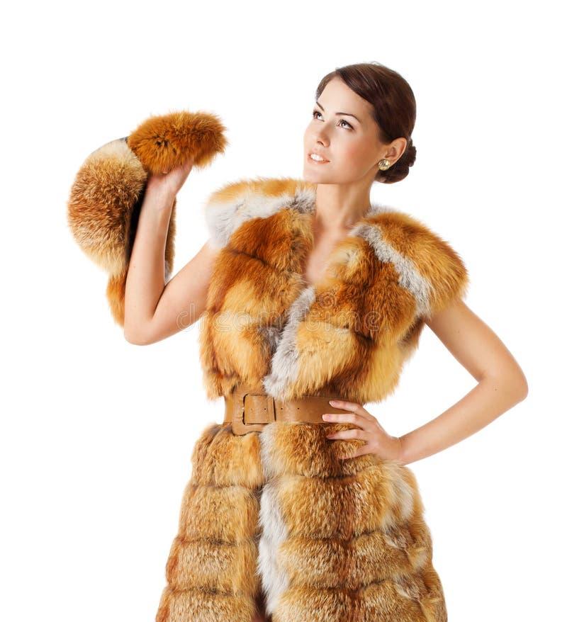 Woman in fox fur coat, holding winter fur hat. Isolated white background. Woman in fox fur coat, holding windows fur hat. Isolated white background royalty free stock image