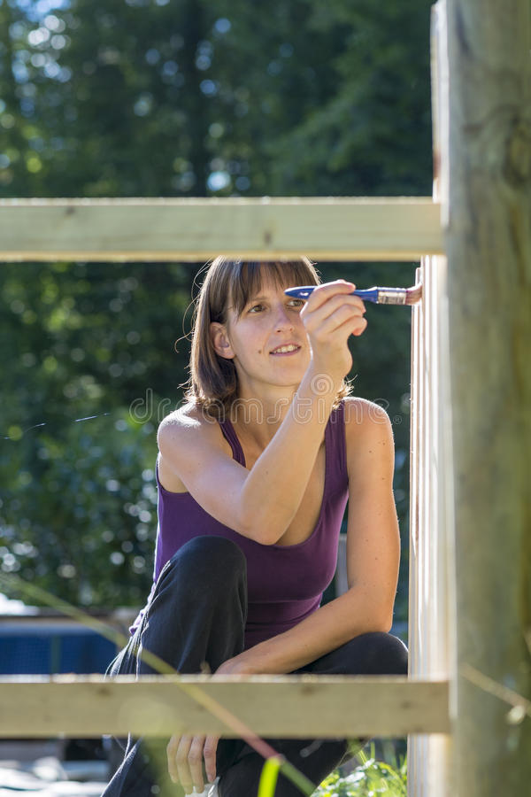 Woman framed by fence using brush to paint on wood royalty free stock images