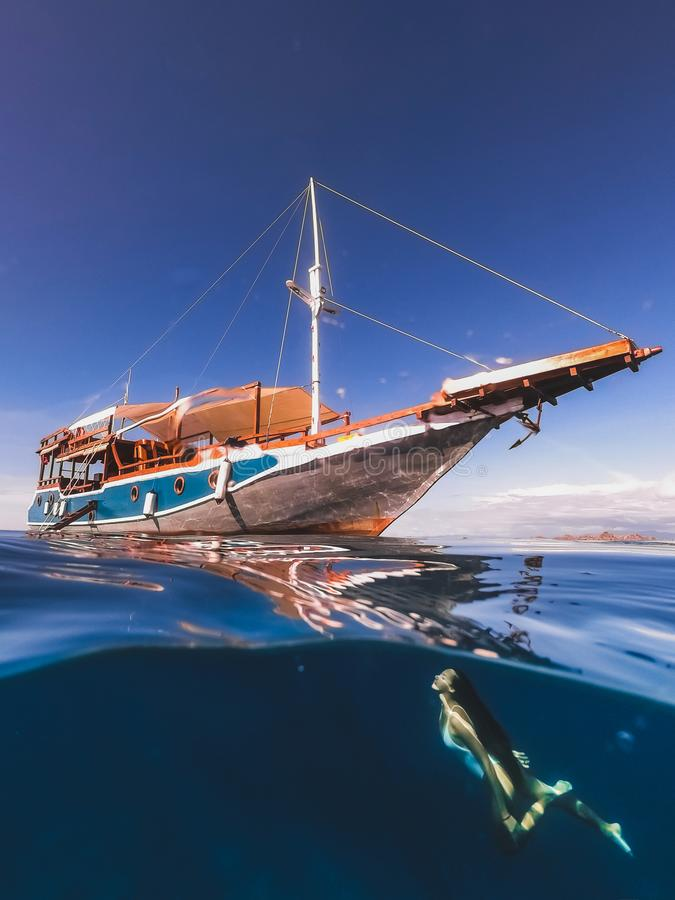 Woman free diving underwater with yacht half view stock images