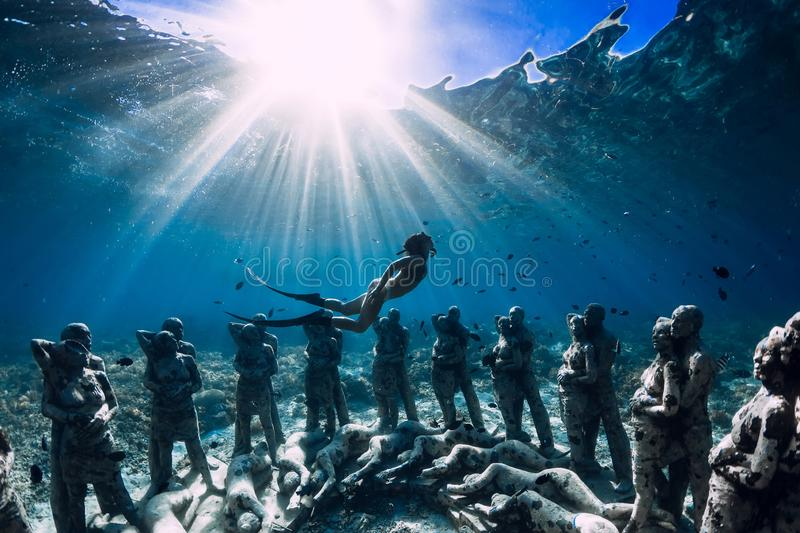 Woman freediver with fins dive near underwater statues. Underwater tourism in the ocean. royalty free stock image