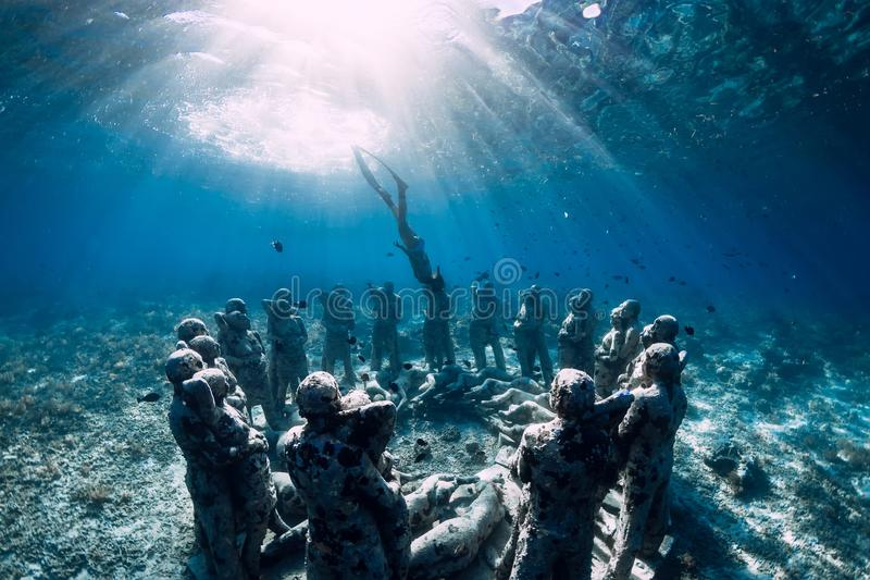 Woman freediver with fins dive near underwater statues. Underwater tourism in the ocean. stock photo
