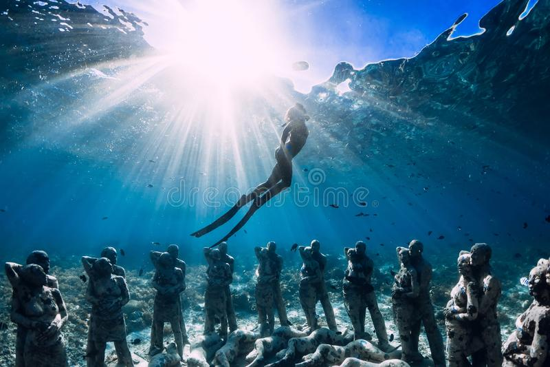 Woman freediver with fins dive near underwater statues. Underwater tourism in the ocean. royalty free stock photography