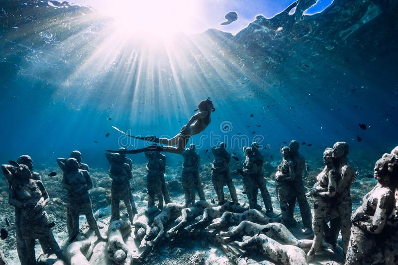 Woman freediver with fins dive near underwater statues. Underwater tourism in the ocean. stock image