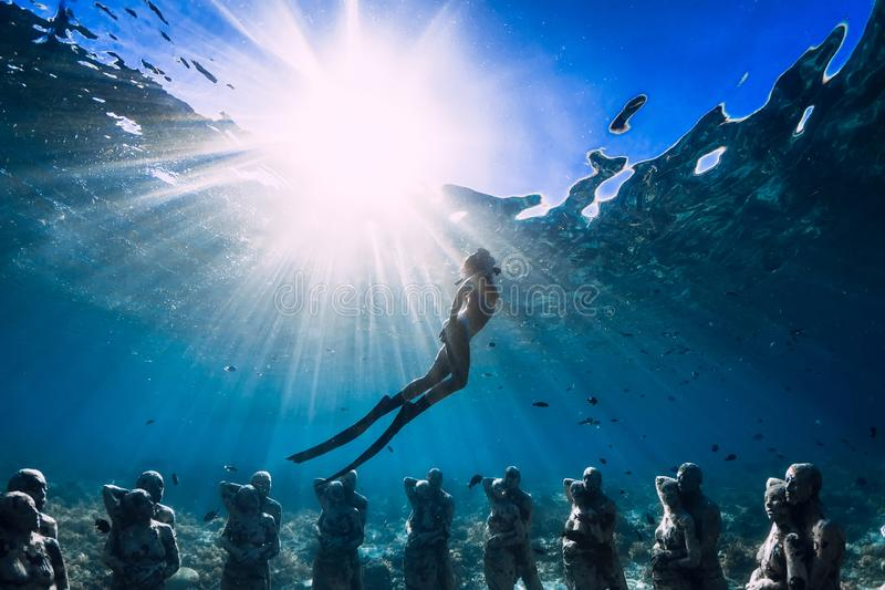 Woman freediver with fins dive near underwater statues. Underwater tourism in the ocean. royalty free stock photo