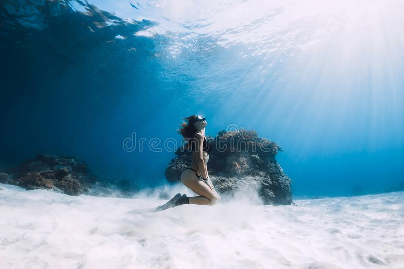 Woman freediver with fins over sandy sea. Freediving underwater stock photography