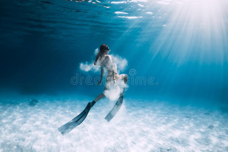 Woman freediver with fins and white sand over sandy sea. Freediving underwater stock image