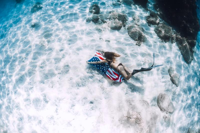 Woman freediver glides over sandy sea bottom with United States flag. Independence day stock images
