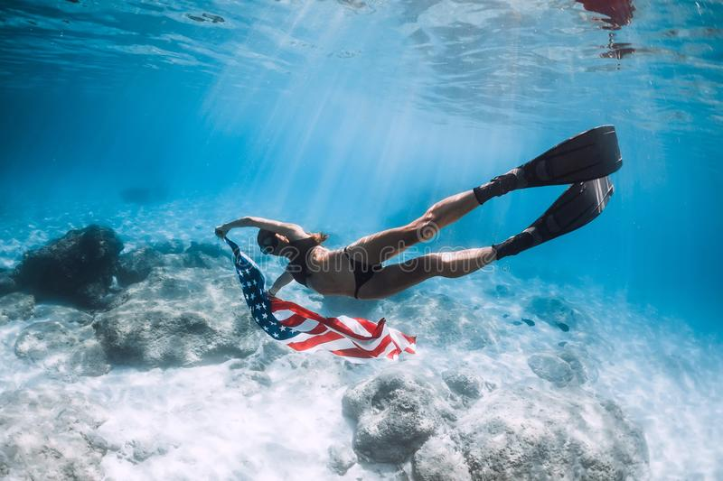 Woman freediver glides over sandy sea bottom with United States flag. Independence day stock photography