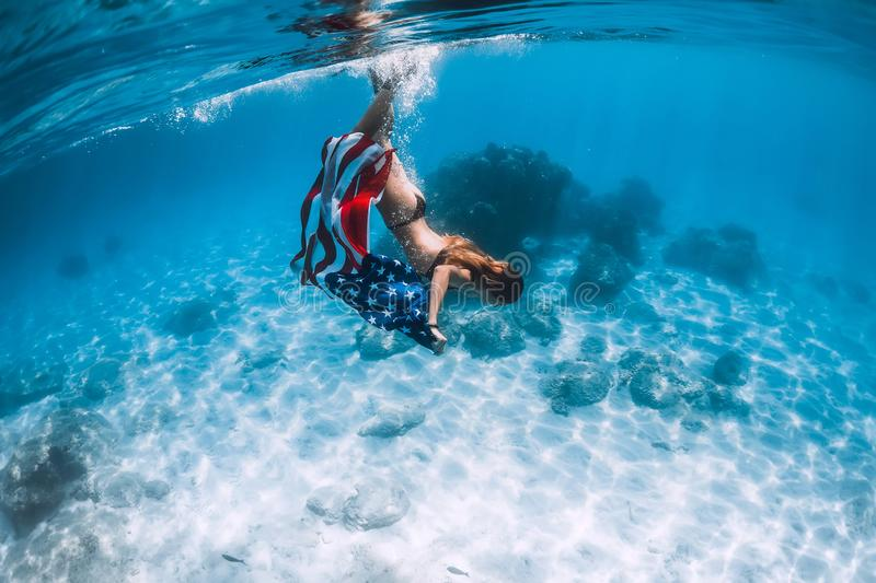 Woman freediver glides over sandy sea bottom with United States flag. Independence day stock image