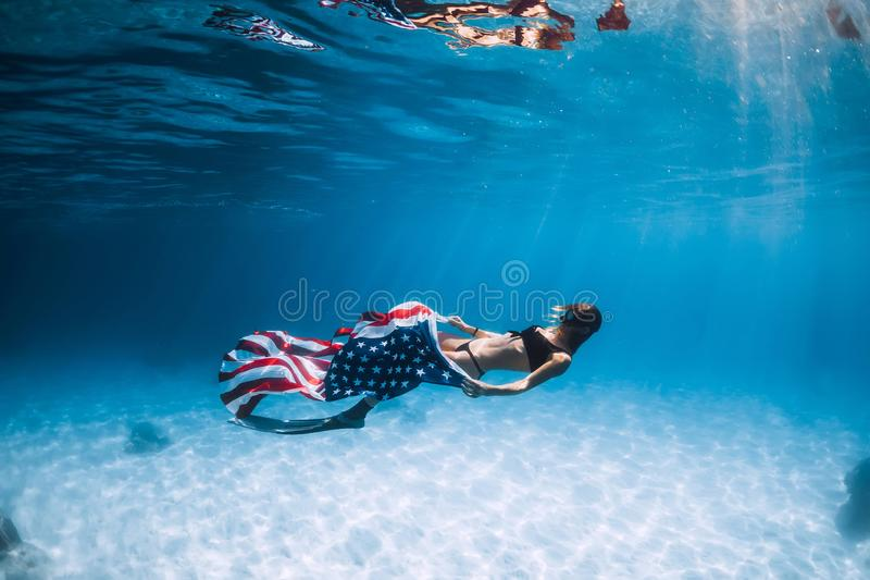 Woman freediver glides over sandy sea bottom with United States flag. Independence day royalty free stock photography