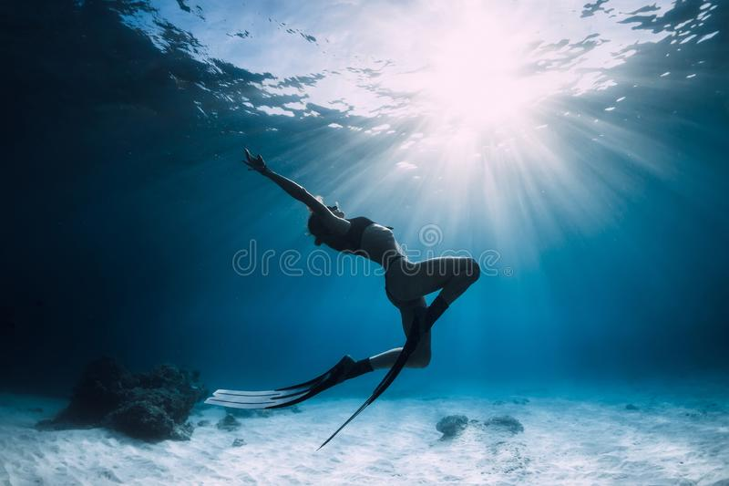 Woman freediver over sandy sea with fins stock images