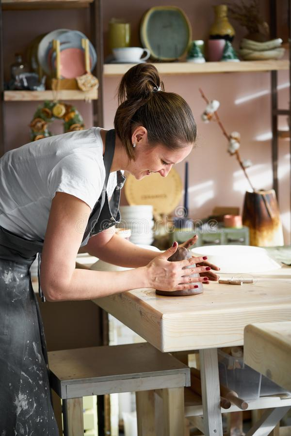 Woman freelance, business, hobby. Woman making ceramic pottery on table in studio stock photos