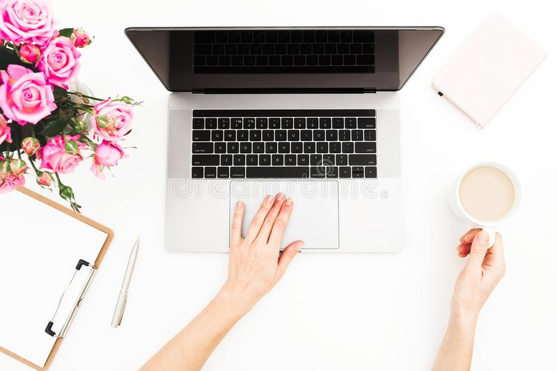Woman freelancer working on laptop. Workspace with female hands, laptop, pink roses bouquet, coffee mug, diary on white table. Top royalty free stock image