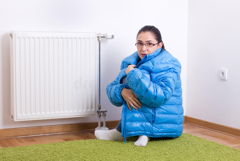 Woman freezing next to radiator royalty free stock photography