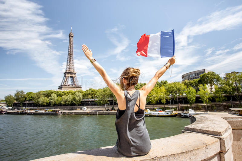 Woman with french flag in Paris. Young stylish woman with french flag enjoying great view on the Eiffel tower sitting back on the bridge in Paris royalty free stock image