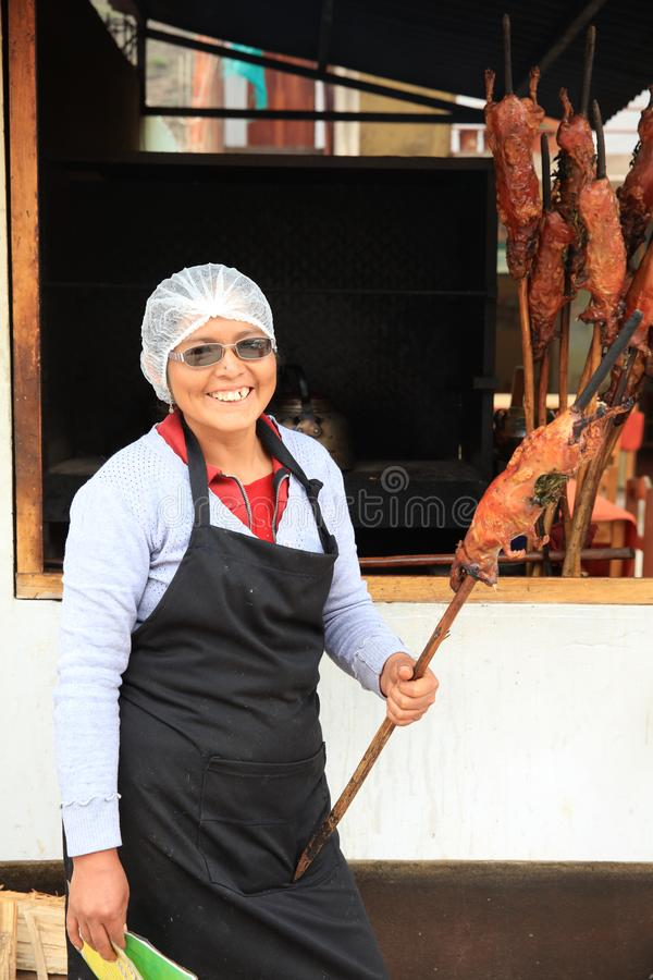 Woman with fresh roasted Guinea Pig in Lamay. Its a traditional Meal in Peru royalty free stock images