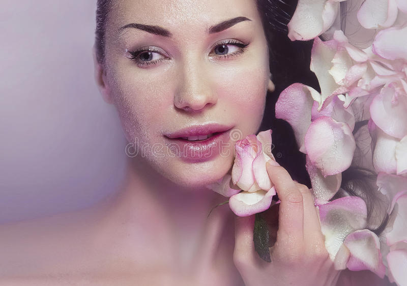 Woman with Fresh Rose petals and pink rosebud. Natural Rose water. Woman with clean Healthy skin. Fresh Rose petals and pink rosebud. Natural Rose water for stock images