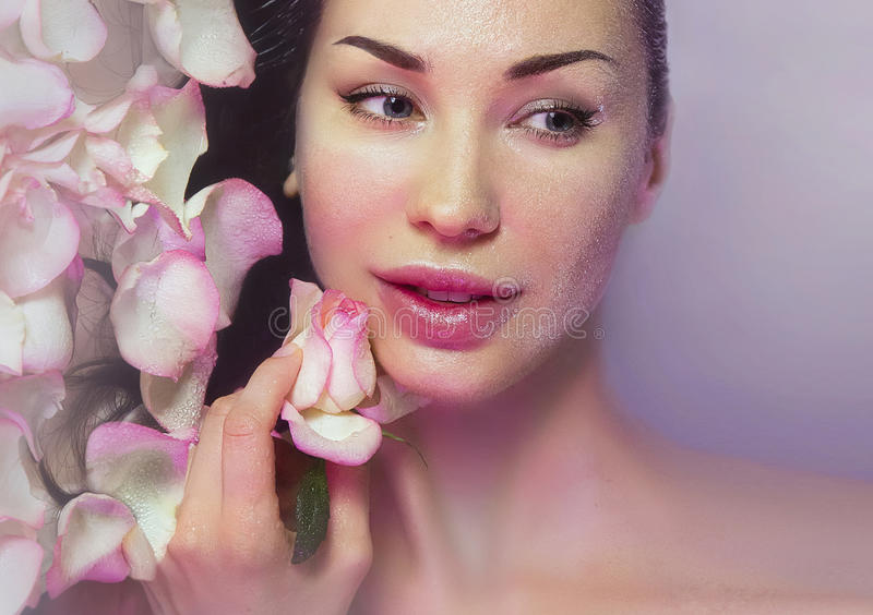 Woman with Fresh Rose petals and pink rosebud. Natural Rose water. Woman with clean Healthy skin. Fresh Rose petals and pink rosebud. Natural Rose water for stock image